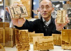 神戸らしい風景の図柄を施した木製名刺ケースと開発者の本岡幸二さん=神戸市中央区中町通4