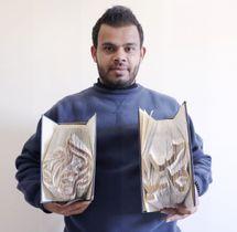 アラビア語の文字の作品(右)と中東の衛星テレビ「アルジャジーラ」のロゴマークをモチーフにした作品(左)を持つアハマド・フメイドさん=3月、パレスチナ自治区ガザ市南部ヌサイラート(共同)