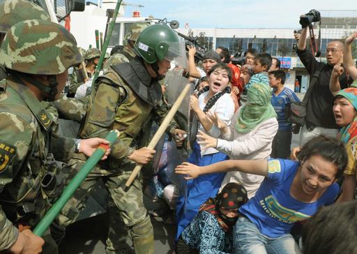 2009年7月、中国・新疆ウイグル自治区ウルムチで警官とぶつかる住民たち(共同)