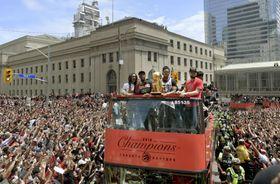 NBA決勝を制し、優勝パレードで沿道のファンに祝福されるラプターズの選手ら=トロント(USA TODAY・ロイター=共同)