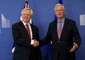 19日、ブリュッセルのEU本部で握手するEUのバルニエ首席交渉官(右)と英国のデービス離脱担当相(AP=共同)