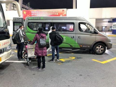 上海市の空港から隔離ホテルに向かう中国人ら