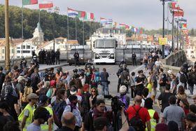 24日、フランス南西部バイヨンヌで、警察が封鎖した橋付近に集まるデモ参加者(AP=共同)