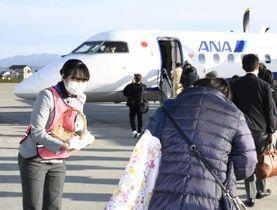 桃の節句に合わせて乗客にひなあられを配る全日空の女性職員=3日午後、松山市南吉田町