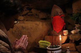 洞窟内の観音像に手を合わせる参拝者=長崎県新上五島町、岩家観音