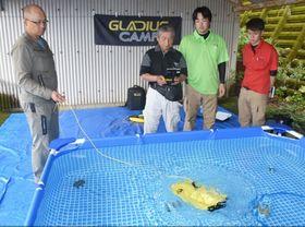 水中ドローンの操作法を学ぶ講習会参加者ら=志布志市の志布志自動車学校