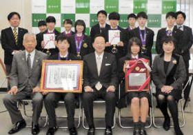 賛辞の楯を贈られた加藤校長(前列中央)と陸上競技部の選手ら