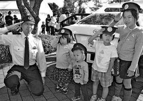 警察官の制帽をかぶって敬礼する子ども=徳島市の四国大