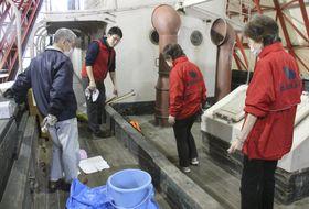 「第五福竜丸」の船体を掃除する展示館職員ら=9日、東京都江東区