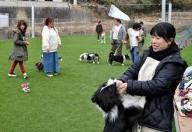 被災後、半年ぶりの営業を再開したドッグランで犬をあやす大江さん(右端)