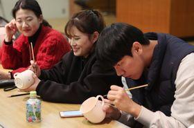 絵付け体験する外国人留学生=佐世保市、三川内焼伝統産業会館