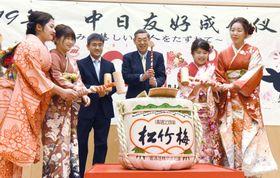 北京の日本大使館で開かれた「日中友好成人式」で、横井裕駐中国大使(右から3人目)と鏡開きをする新成人ら=12日(共同)