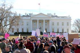 20日、米ワシントンのホワイトハウス前でトランプ大統領に抗議するデモ隊(共同)