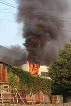 炎と黒煙が上がる豊島繊維の工場の火災現場=20日午後6時37分、福井県永平寺町