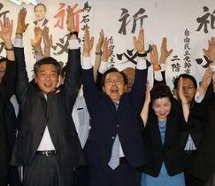 万歳して再選を喜ぶ石井氏(中央)=21日午後8時9分、岡山市北区