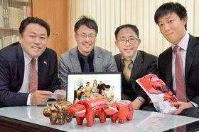 シリアの子どもたちが制作した赤べこを矢部副町長(左)に届けた(左から2人目から)佐藤さん、青山さん、木戸さん