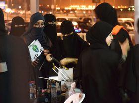 12日、サウジアラビア西部ジッダの競技場で、入場前に手荷物検査を受ける女性(共同)