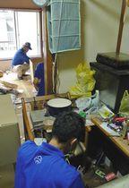 孤立死した男性の部屋で遺品を整理する遺品整理専門会社の従業員ら=東京都豊島区で
