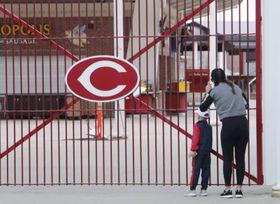 本来ならば大リーグが開幕するはずだった3月26日。門が閉ざされた球場の中をのぞき込むレッズのファン=シンシナティ(USA TODAY・ロイター=共同)