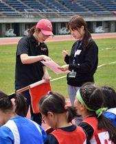 15日に行われた陸上大会で経験者のスタッフに指導を受けながら、大会運営を補助した函館短大の学生(右)