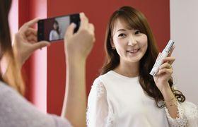 紹介する商品を手に、スマートフォンで撮影してもらう「インフルエンサー」の能美黎子さん=東京都渋谷区