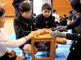 指導を受けながら木のたまごを作る児童=22日、長門市
