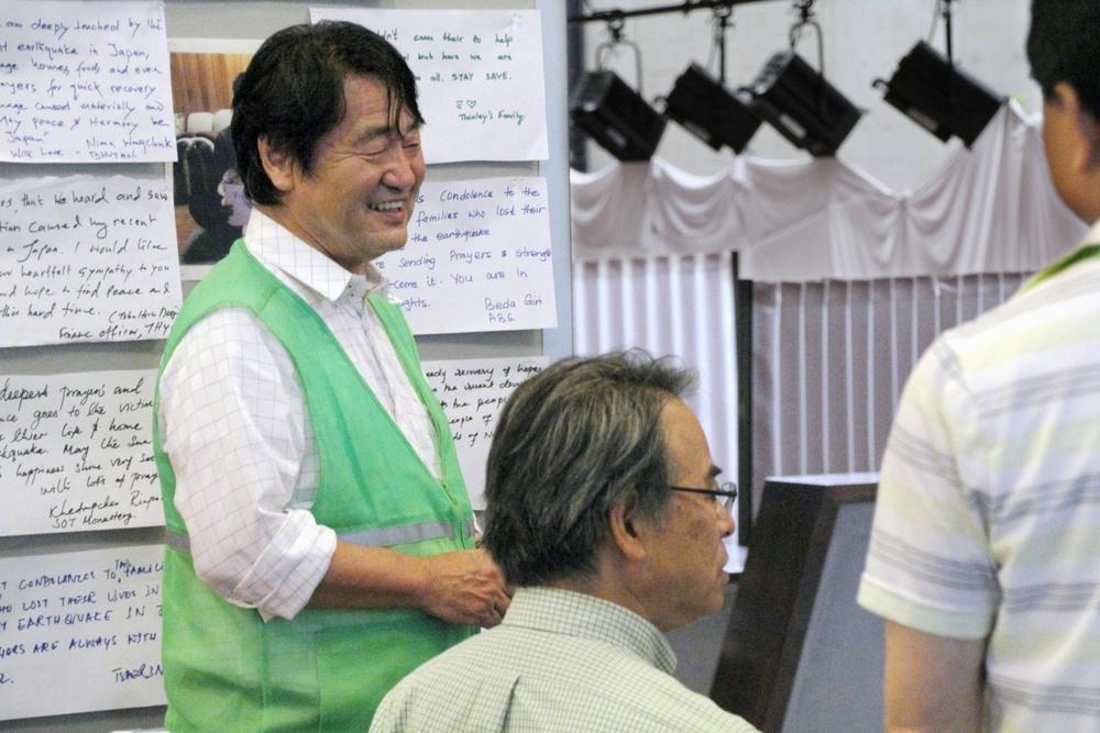 熊本学園大の避難所で関係者と話す花田昌宣さん(左)。教職員は緑のベストだ=熊本学園大提供