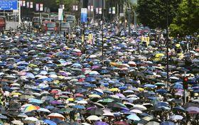 「覆面禁止法」の撤廃などを求めデモ行進する大勢の人たち=20日、香港・九竜地区(共同)