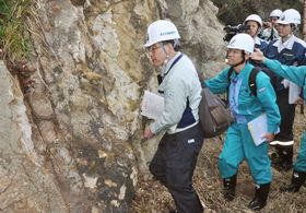 島根原発2号機の現地調査で、あらわになった地層を調べる原子力規制委の委員ら=2015年10月29日、松江市