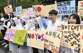 7月26日、ソウルの日本大使館前で日本製品の不買運動をする韓国の高校生ら(共同)