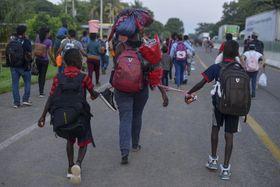 12日、メキシコ南部チアパス州で、バッグを背負って歩く移民ら(AP=共同)
