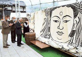 開帳された観音大曼陀羅に手を合わせる参拝者=沼津市千本緑町の長谷寺