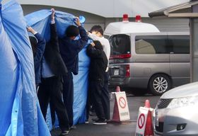 青森県八戸市で女子児童が切り付けられた事件で、送検のため青森県警八戸署を出る男子生徒を乗せた車(右)=14日午前9時36分