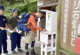 南国署が設置した入山ポストで用紙に記入する登山者(香美市物部町の光石登山口)