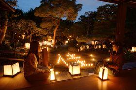 京都・妙心寺塔頭の東林院で、ろうそくやあんどんの明かりに照らされ浮かび上がる庭園=5日夕