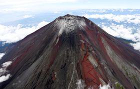 今シーズン初めて山頂付近が雪化粧した富士山。山梨県富士吉田市が「初雪化粧」を宣言した=21日午前(共同通信社ヘリから)