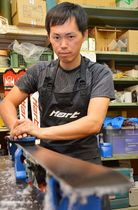 湯浅選手のスキー板をメンテナンスする横田幸平さん=岐阜県御嵩町で