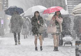 雪の積もった東京・表参道を歩く女性たち=22日午後