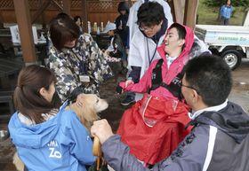 旭山動物園の夜間特別開園に参加し、ゴールデンレトリバーと触れ合う武田翔太さん(右から2人目)=22日午後、北海道旭川市