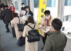 大阪からの到着客にかつお加工品を贈る枕崎市の関係者=霧島市の鹿児島空港