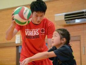 町地域おこし協力隊員として、子どもにバレーを教えるヴォレアス選手の辰巳さん=10日、北野小体育館