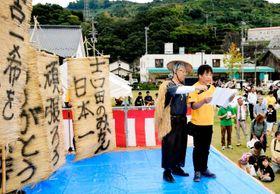 「武左衛門一揆の道」で吉田地域に到着し応援メッセージを掲げたむしろをバックにあいさつする中川会長(右)