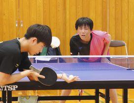 中国・撫順市第一中学の部員(左)と卓球で交流を深める富山中部高の部員=富山中部高で