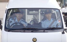 送検のため、佐藤竜彦容疑者を乗せ愛知県警豊田署を出る車両=15日午前8時30分