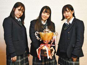 高校生ダンス大会でグランプリを獲得し、ポースを取る東葉高ダンスドリル部の3人=船橋市役所で
