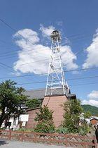 中野陣屋・県庁記念館前に立つ高さ18メートルの鉄骨警鐘楼=中野市中央