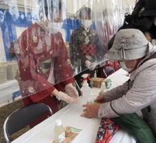 大安寺の「笹酒祭り」で拝観者(右)に日本酒などを配る笹娘=23日午前、奈良市