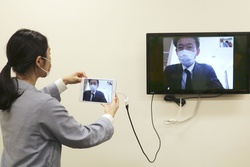 軽症者宿泊施設のオンライン診療室(画面)とスタッフルームを映像でつなぐデモンストレーション=4月、大阪市住之江区のホテル(大阪府看護協会提供)