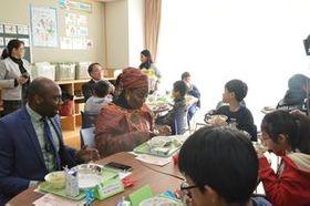 ナイジェリア料理の給食を味わう大使館関係者と児童ら