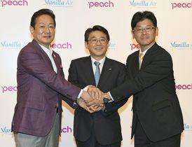 記者会見で握手する(左から)ピーチ・アビエーションの井上慎一CEO、ANAHDの片野坂真哉社長、バニラ・エアの五島勝也社長=22日午後、東京都港区